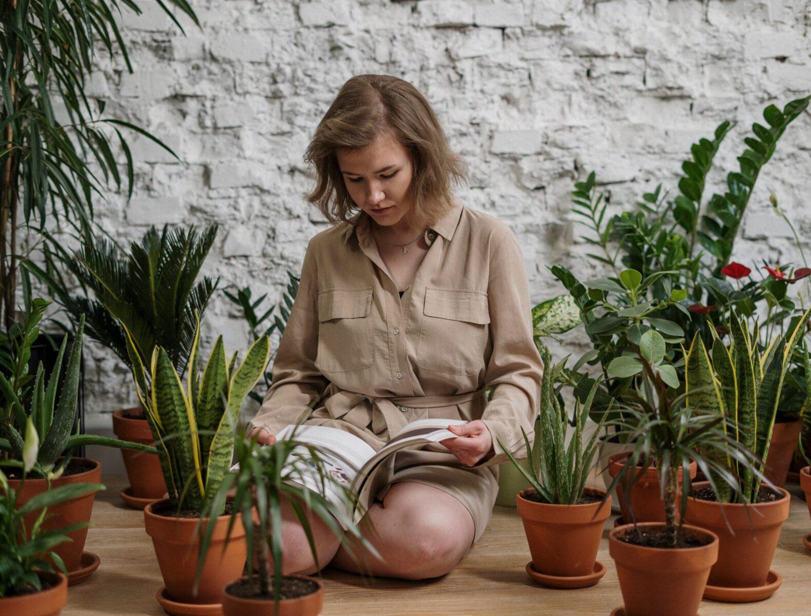 Vrouw zit op de grond tussen duurzame kamerplanten